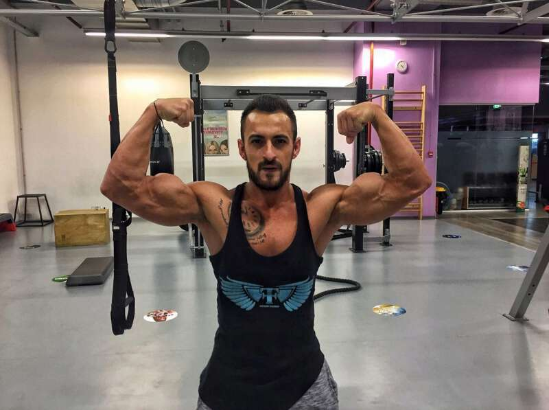 Antonio Ricky flexing his muscles at the gym